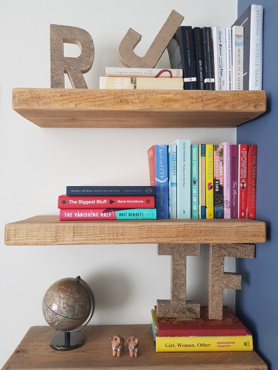 3 wooden shelves with books. first shelf also has a small world globe, two mini bull ornaments and 3D I and F decorated cardboard letters. Second shelf is colour coordinated books. Final shelf has cardboard letters R & J with more books