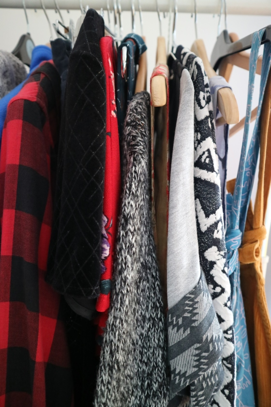 Close up of clothes rail with an assortment of colourful clothes on wooden and plastic hangers
