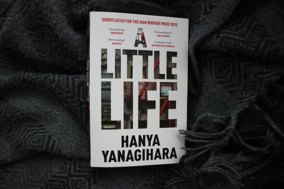 Paperback copy of A Little Life by Hanya Yanagihara on a grey tasseled blanket