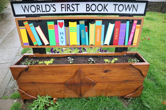 Wooden planter that is placed on grass next to pavement slabs. There are small green plants coming through in the soil of the planter, in a row. The planter is rectangular. The planter has a sign attached above it. The first part is an illustration with an array of colourful book spines, one them says HAY, then KING, then ANTIQUES, then BOOKS, then the second to last book on the right says RIVER WYE. Above this is another sign with a black border which says in black - WORLD'S FIRST BOOK TOWN
