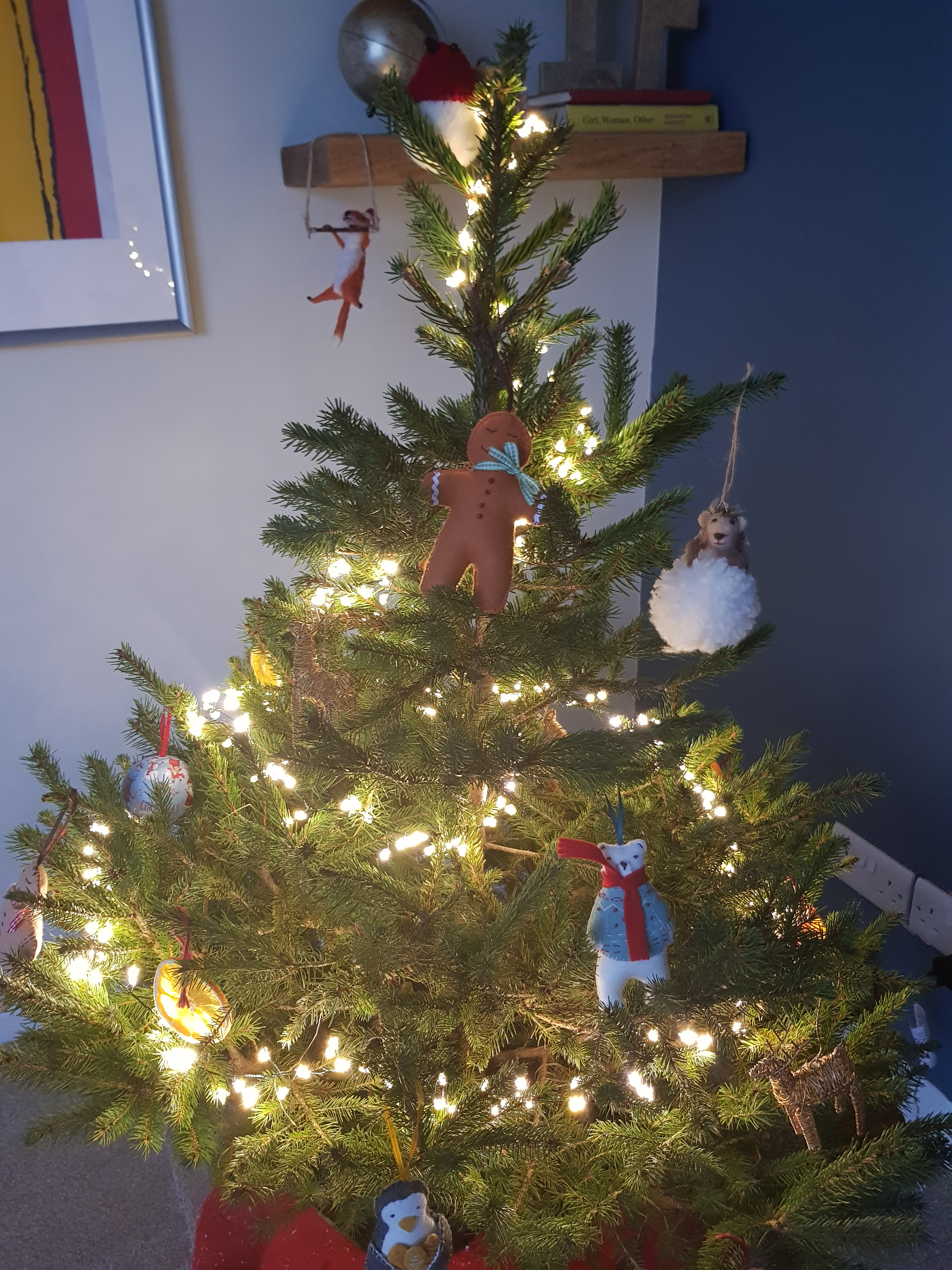 Natural Christmas Tree with fairy lights wrapped round it and an assortment of baubles. In the background on the left is the edge of a silver frame with part of a yellow and red screen print. On the right is a shelf with a globe, books and a felt fox with a christmas hat.
