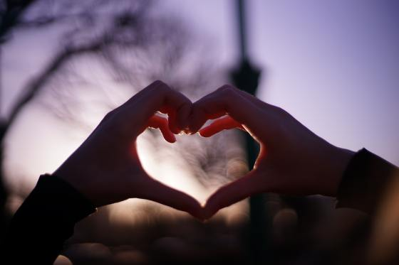 persons hands forming heart, outside with blurred tree and lamp post in background