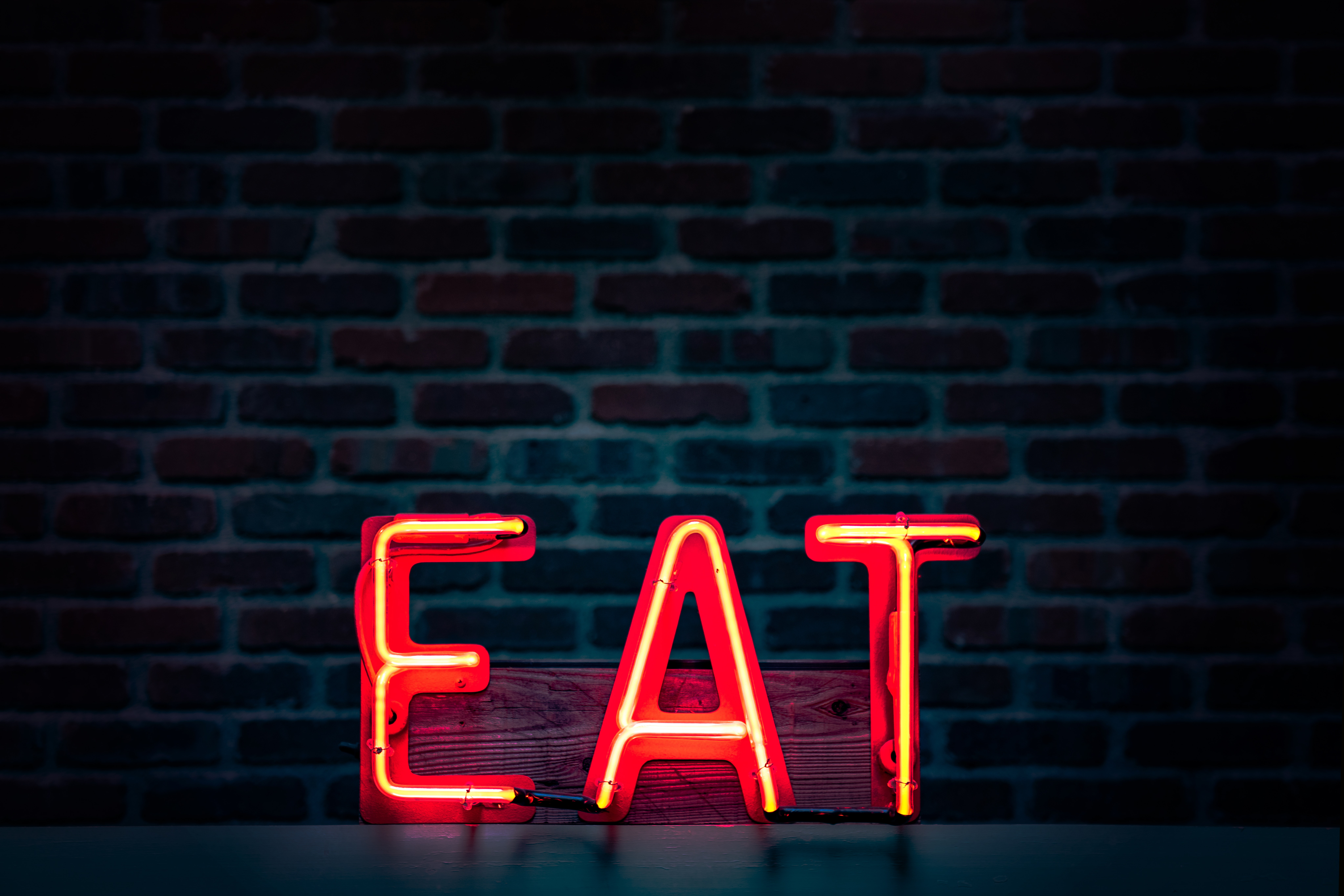 neon sign against a brick wall which says EAT. Neon sign has a red background and text is in yellow