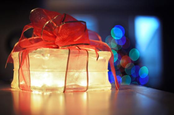 Lighted box wrapped in a large red and gold bow on a brown surface, with twinkly lights from Christmas tree in the background