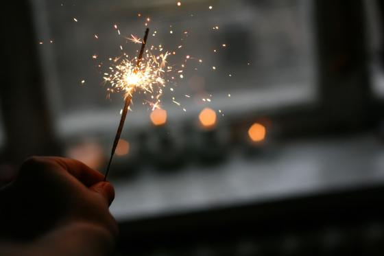 Hand holding a sparkler which is half way through burning. There are sparks flying off the sparkler. The background is blurred but it appears to be that the sparkler is being burned indoors as there is an outline of a window and a windowsill