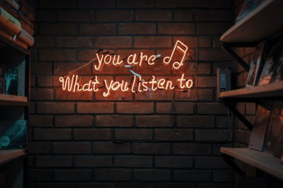 "On a brick wall with wooden shelves on either side is a lighted neon sign that says ""you are (music note then new line) What you listen to"". There are only a few books on the shelves, some with the covers facing, others on their sides stacked on top of each other."