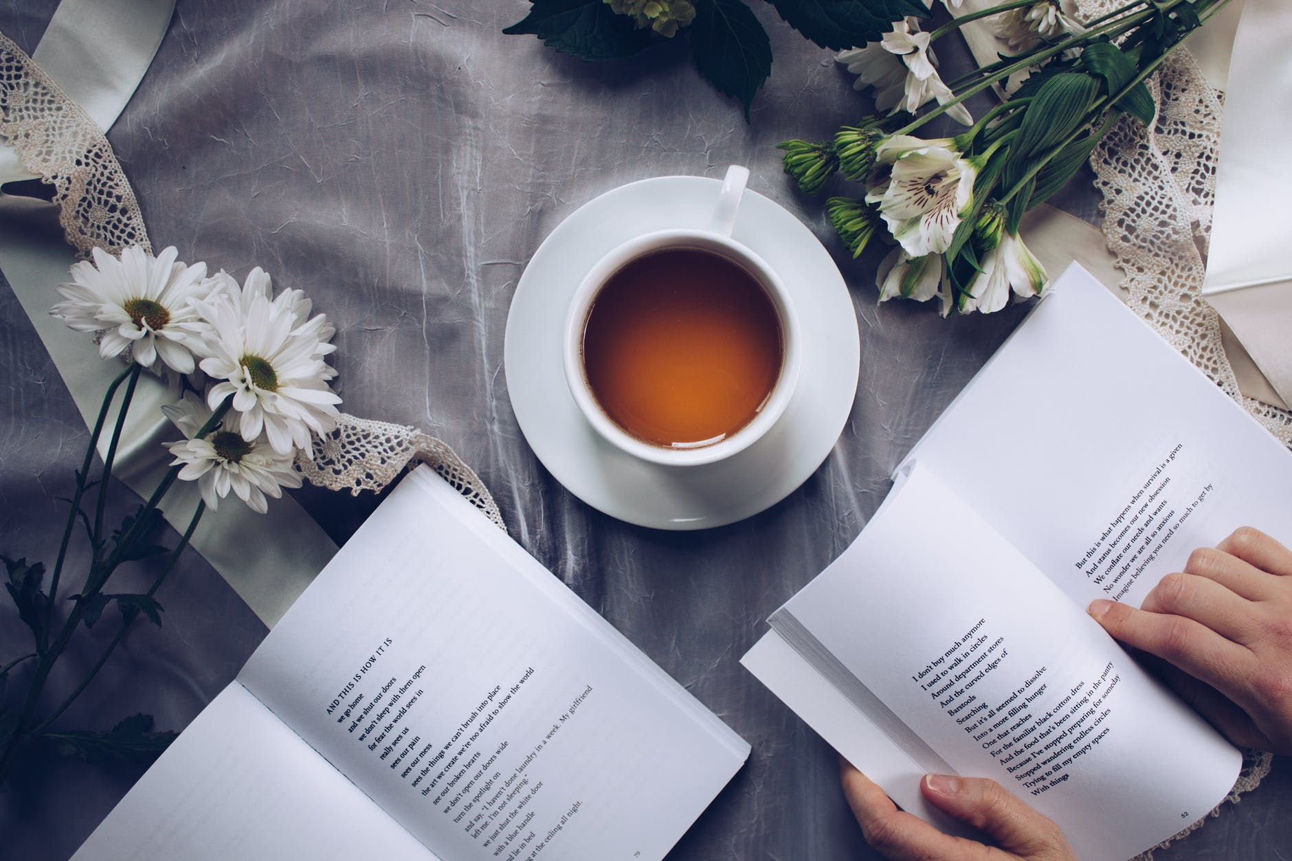 Birds eye view of a close up of a table with a cup of tea in a white mug on a white coaster in the middle. In the foreground our two books open - the book to the right has hands on it, holding it open. There is a sheer table cloth underneath and an arrangement of flowers in the top right hand and left hand corner
