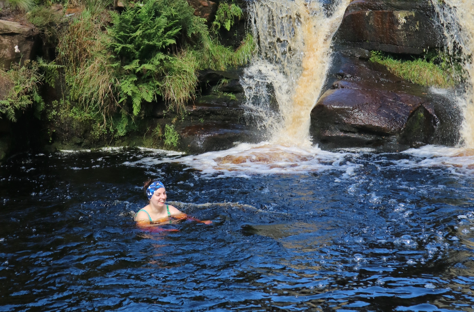 Woman has huge smile on her face as she immerses herself in cold water. You can see her shoulders and swimming costume straps. She has her hair tied up and wears a blue, patterned head band. Behind her is green folliage and part of a waterfall, cascading over rocks