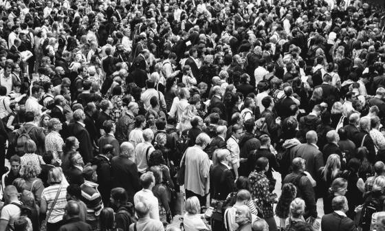 black and white photo filled with a crowd of people mainly turned away from the camera. There is one man at the bottom, front of the photo who is looking in a different direction and you can see half his face